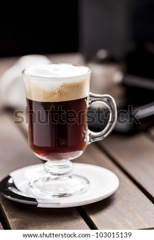 A cup of Cappuccino on a wooden table.