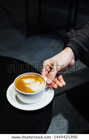 A cup of cappuccino on the table. man's hand holding a cup of cappuccino on the table. #1449425900