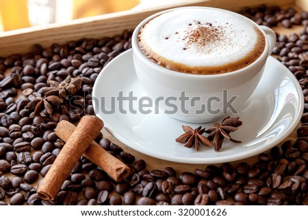 A cup of cappuccino with coffee beans #320001626