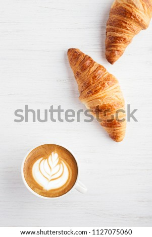 A cup of cappuccino with latte art and two croissants on white wooden table. Traditional french breakfast. Top view. #1127075060