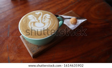 A cup of cappuccino with latte art, cookies, and spoon on wooden background. Beautiful foam, greenery ceramic cups, stylish toning, place for text.