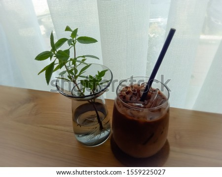 A cup of cocoa on the table next to a glass of water containing a flower decorated with a vase. #1559225027