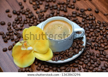 a cup of coffe combined with the beauty of yellow orchid flowers