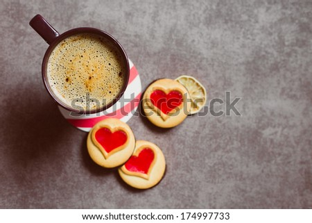 A cup of coffe standing on a table with some cookieis with heart-shaped red jam. Good morning! Lovers\' breakfast