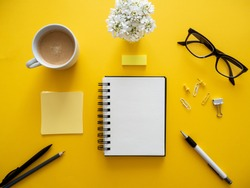 A cup of coffee, a blank notebook, reading glasses and office supplies on a yellow background, top view, everyday office life