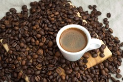 A cup of coffee among selected and calibrated Arabica coffee beans scattered on a napkin, table, blended, top view