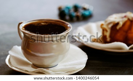 A Cup of coffee and a fresh cake on a saucer. Close up. Morning invigorating drink in a cafe or restaurant. Beautiful delicate photo for romanticism.