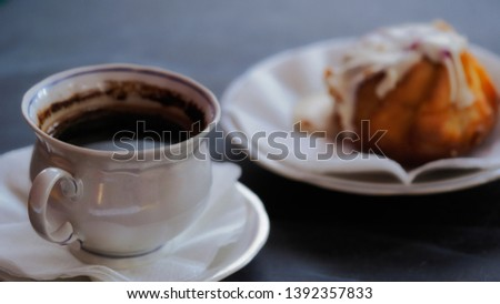 A Cup of coffee and a fresh cake on a saucer. Morning invigorating drink in a cafe or restaurant. Beautiful delicate photo for romanticism.