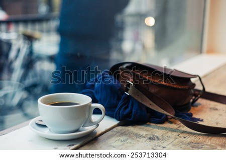 A cup of coffee and a handbag by a window in a cafe
