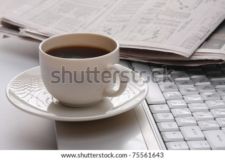A cup of coffee and a newspaper on a laptop