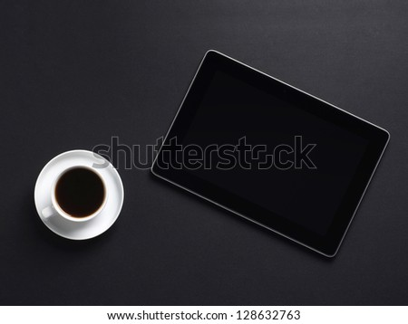 A cup of coffee and a tablet pc over the black background
