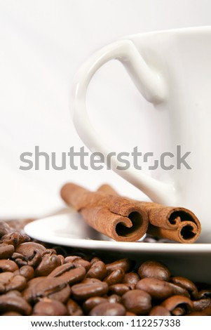 A cup of coffee, and cinnamon, coffee beans around it.