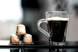 A cup of coffee and coffee capsules at the window.
