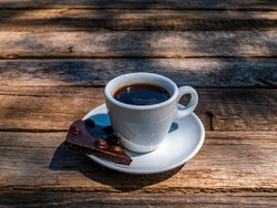 A cup of coffee and dark chocolate in a saucer on a wooden table. Coffee drink. Dark chocolate bar. Cup and saucer. Wooden table from a bar. Food and drinks. Ceramic tableware. Street Cafe.
