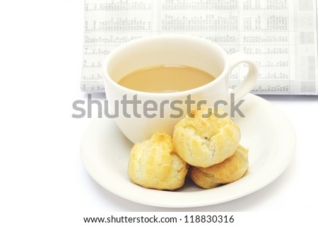 a cup of coffee and eclairs against newspaper