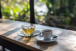 A cup of coffee and tea on wooden table