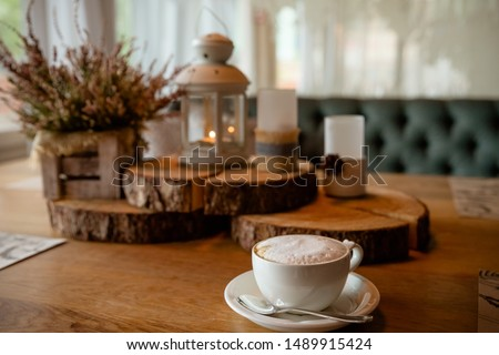 A cup of coffee, cappuccino and autumn decor on table.Hello Autumn. Autumn decor, fall mood, atmosphere of autumn. Candles, pink heather and floristic art decoration. #1489915424