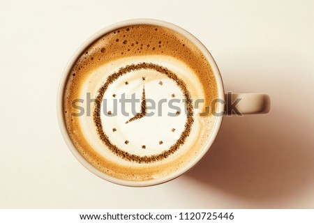 a cup of coffee cappuccino with a clock pattern from cinnamon on milk foam #1120725446