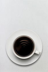 A cup of coffee full of fresh black american espresso with wi-fi sign.