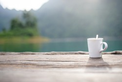 a cup of coffee in a blurry riverside view landscape background in sunshine with narrow depth of field