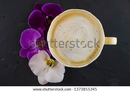 A Cup of coffee in a cozy style with a white and purple orchid. Dark background.