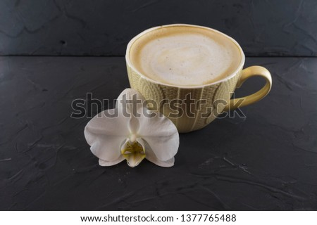 A Cup of coffee in a cozy style with a white orchid. Dark background.