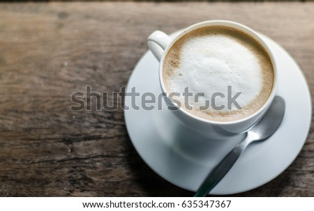 A cup of coffee in a white cup on wooden background #635347367