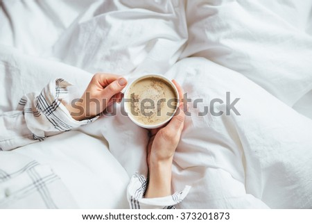 A cup of coffee in their hands in bed on a white blanket, simple, home, space in the frame