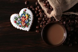 A cup of coffee is standing on a wooden table. Next to it lies a jute sack full of coffee and a decorated gingerbread heart.