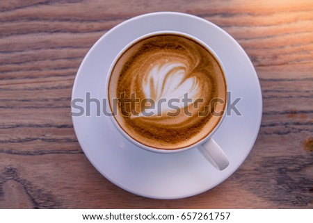 A cup of coffee late art with space on  wood background,vintage picture style