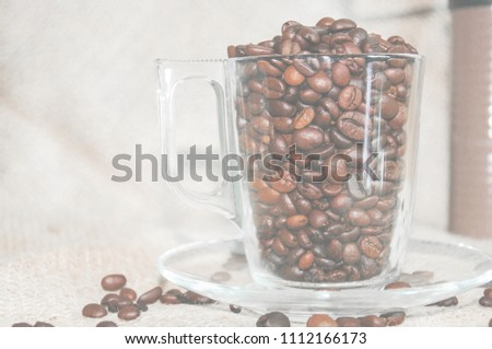 a cup of coffee on a light background, coffee beans, a cheerful morning #1112166173