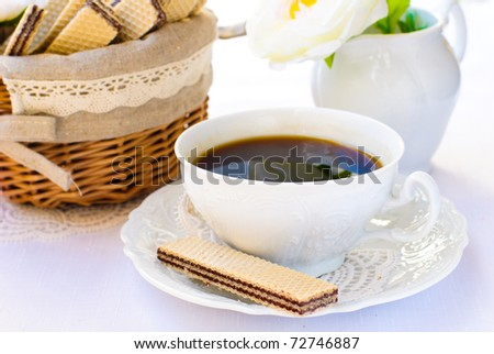a cup of coffee on a saucer and a chocolate wafer