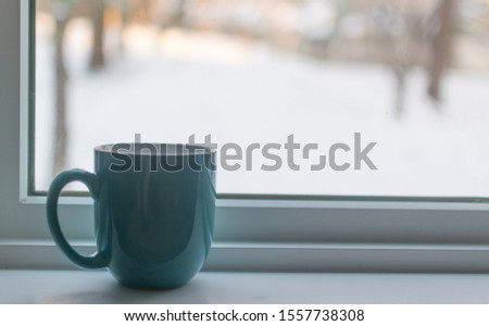 A cup of coffee on a windowsill in the winter