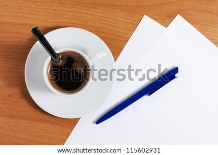 A cup of coffee on a wooden table with blank papers and blue pen, top view