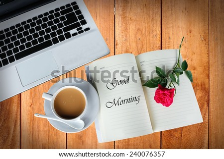 A cup of coffee on wooden table with rose and computer