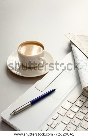 A cup of coffee, paper and a pen on a laptop
