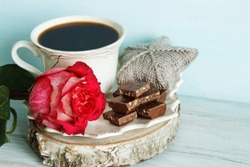 A cup of coffee, pieces of chocolate and a pink rose. Romantic breakfast.