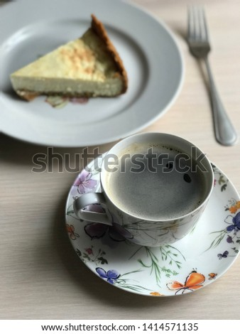 A cup of coffee, slice of cheesecake on the plate and fork on light wooden background. Beautiful delicious morning concept. Food blog recipe picture, sweets shop ad.