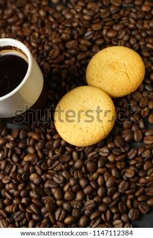 A cup of coffee, snacks of dried oranges and coffee beans on a dark background. Delicious coffee of the best varieties.