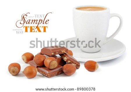 A cup of coffee with a chocolate and nuts on a white background