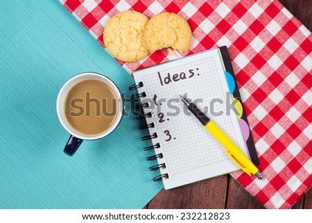 A cup of coffee with biscuits and a list of ideas in a notebook. The idea of coaching, motivation, coaching and achievement.