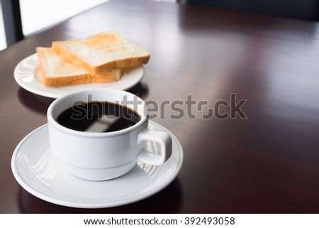A cup of Coffee with bread on table in the morning/selective focus #392493058