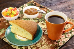 A cup of coffee with cake, candy, candied fruits and jam on a wooden table.