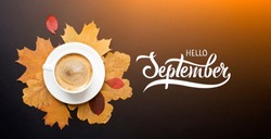 A cup of coffee with cappuccino and autumn leaves composition. Autumn decor, fall mood, autumn still life with hand lettering Hello September.