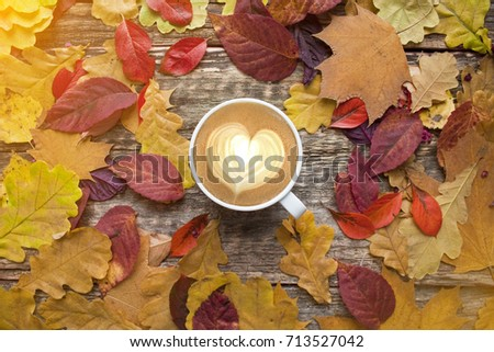 A cup of coffee with cappuccino and autumn leaves on old wooden background. Autumn decor, fall mood, autumn still life.