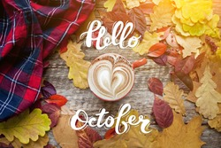 A cup of coffee with cappuccino and autumn leaves on old wooden background with hand lettering Hello October. Autumn decor, fall mood, autumn still life.