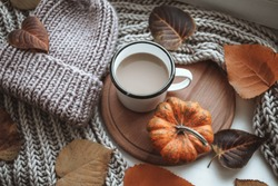A cup of coffee with cappuccino and autumn leaves, pumpkin, warm blanket and beanie hat on a window. Autumn decor, fall mood, autumn still life. Hygge home interior.