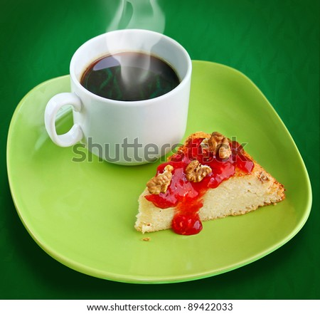A cup of coffee with cheese cake with raspberry jam and nuts on green background