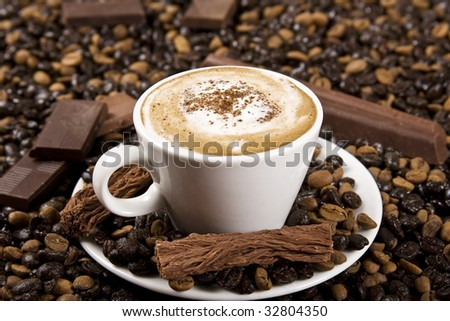 A cup of coffee with chocolate and coffee beans.
