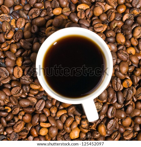 A cup of coffee with coffee bean as background